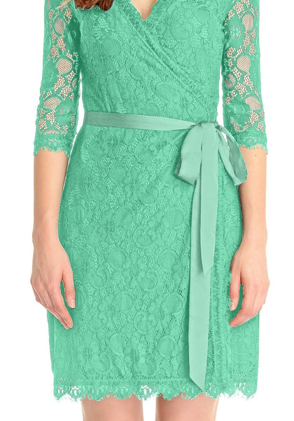 Close up shot of model wearing mint green lace overlay plunge wrap-style dress