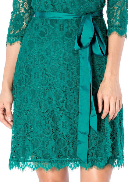 Close up shot of model wearing teal lace overlay plunge wrap-style dress