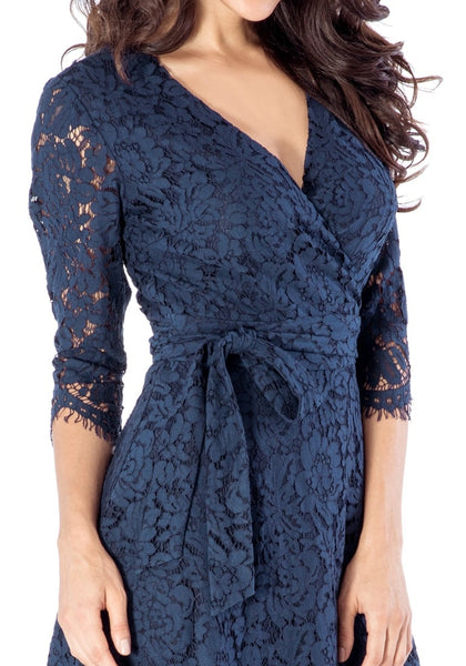 Close up shot of woman wearing navy floral lace overlay wrap dress