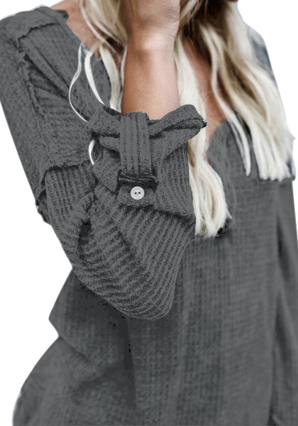 Closeup shot of woman in grey front buttons roll-up sleeves textured top