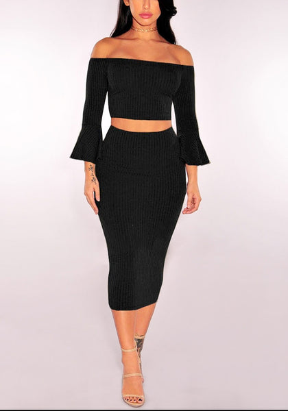 Front full body shot of model in black ribbed knit bell-sleeved two-piece skirt set