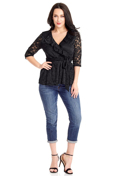 Front full body shot of model in plus size black ruffled faux wrap blouse