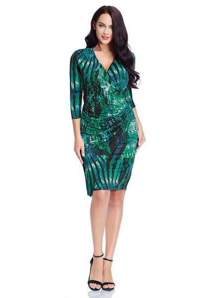 Front full body shot of model in plus size green leaf-printed midi wrap dress