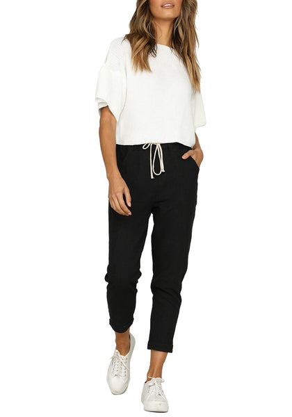 Front full body shot of model wearing black drawstring-waist rolled-up cropped pants