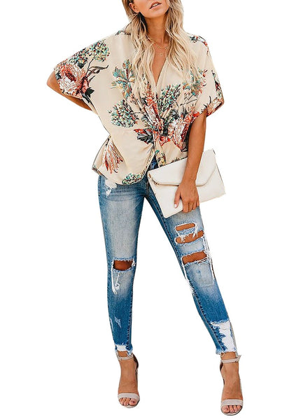 Front full body shot of model wearing navy floral print V-neckline twist-front top