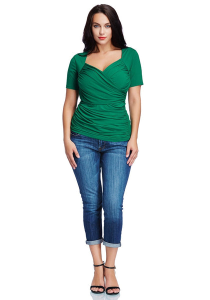 Front full body shot of model wearing plus size green ruched surplice top