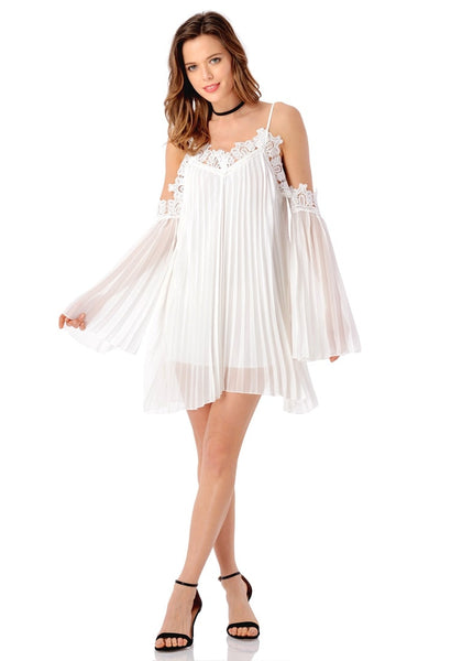 Front full body shot of model wearing white cold-shoulder pleated shift dress