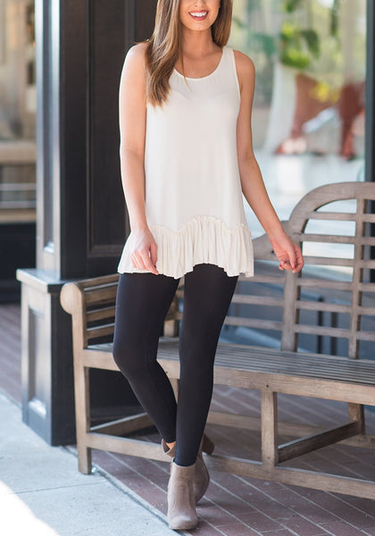 Front full body shot of woman wearing white ruffle-hem crew neck sleeveless tunic