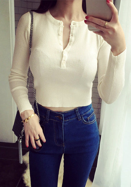 Front of girl in beige ribbed crop top and dark blue jeans