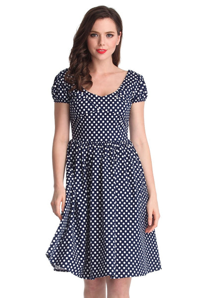 Front shot of a brunette model wearing a navy blue polka dot dress