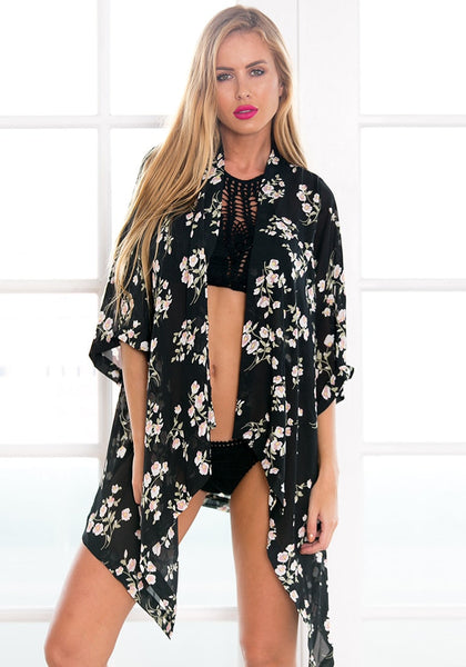 Front shot of blonde model wearing black floral open-front chiffon kimono with black bikini