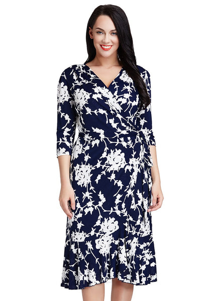 Front shot of brunette woman in plus size blue floral ruffled wrap dress
