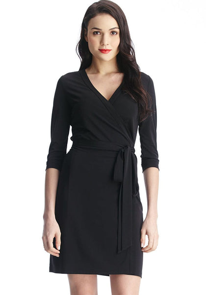 Front shot of dark-haired lady in black plunge wrap-style belted dress