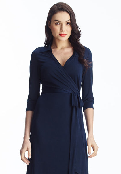 Front shot of dark-haired lady in navy blue plunge wrap belted maxi dress