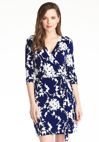 Front shot of lady wearing navy blue floral plunge wrap dress