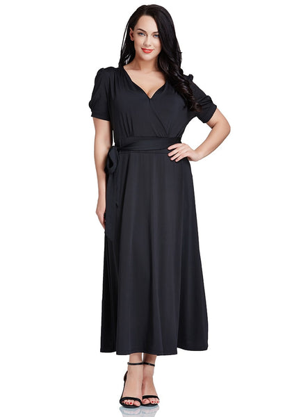 Front shot of model in plus size black surplice belted long dress with one hand at waist