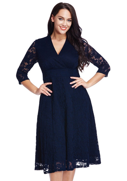 Front shot of model in plus size navy lace surplice midi dress with hands at waist