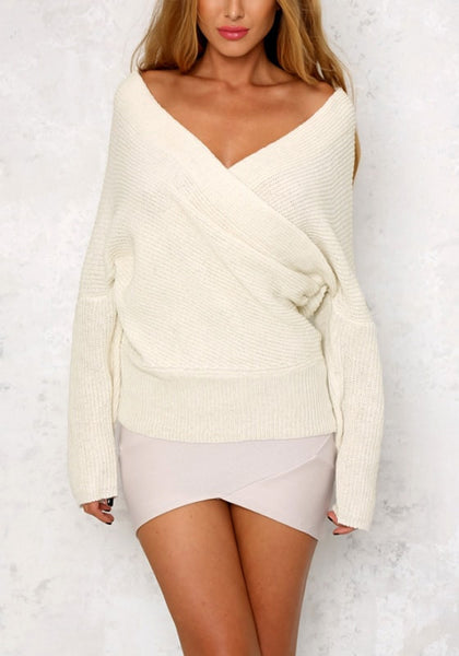 Front shot of model posing in white wrap off-shoulder sweater