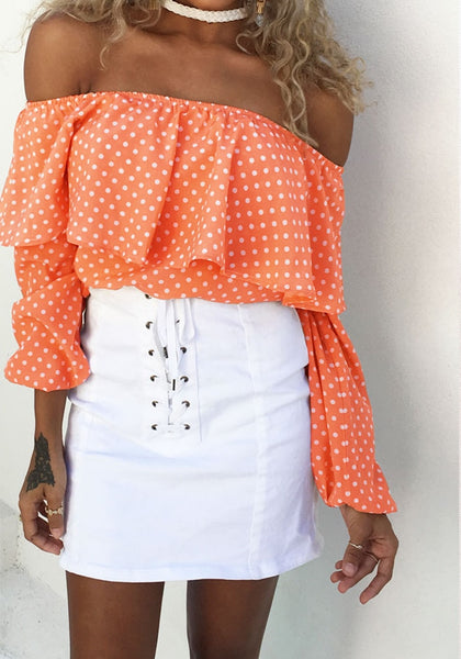 Front shot of tan-skinned model in orange polka dots off-shoulder top