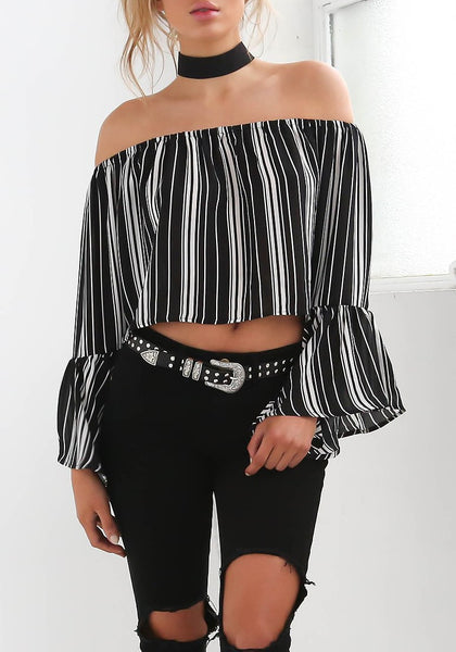 Front shot of woman in striped bell sleeves off-shoulder crop top with black ripped jeans