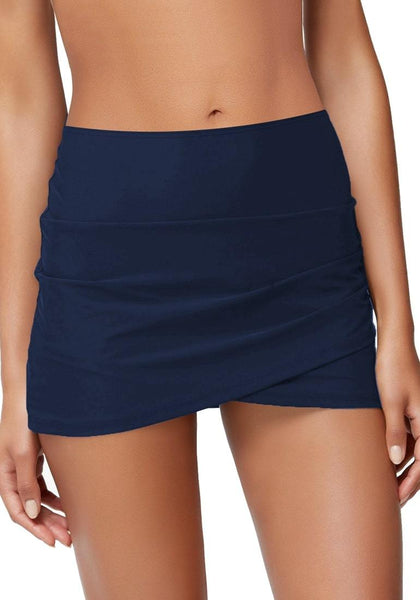 Front vieiw of model wearing navy tulip-hem mid-waist ruched swim skirt