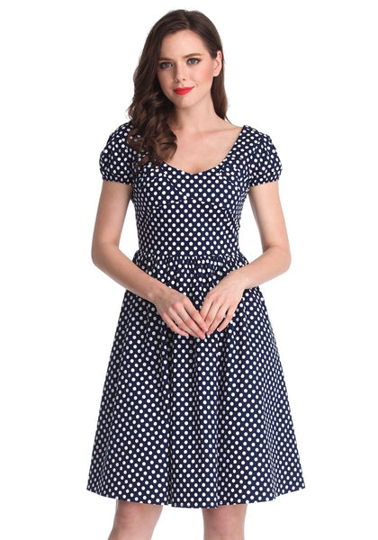 Front view of a brunette model in a navy blue polka dot dress