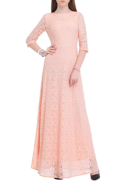Front view of brunette posing in a pink maxi lace dress