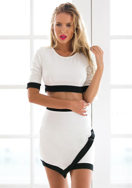 Front view of model in black-lined white two-piece dress