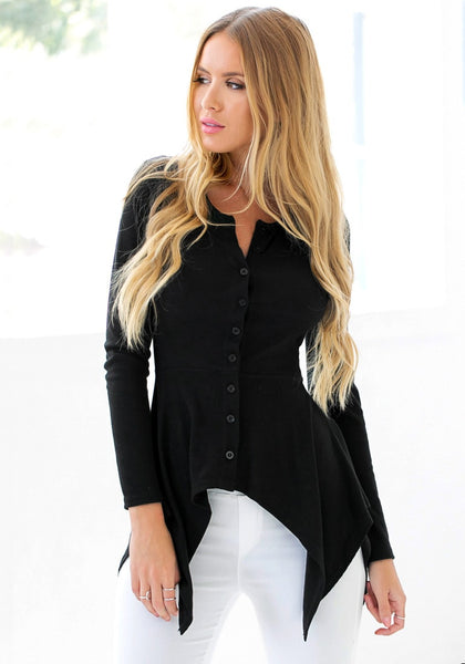 Front view of model in black asymmetrical knit top