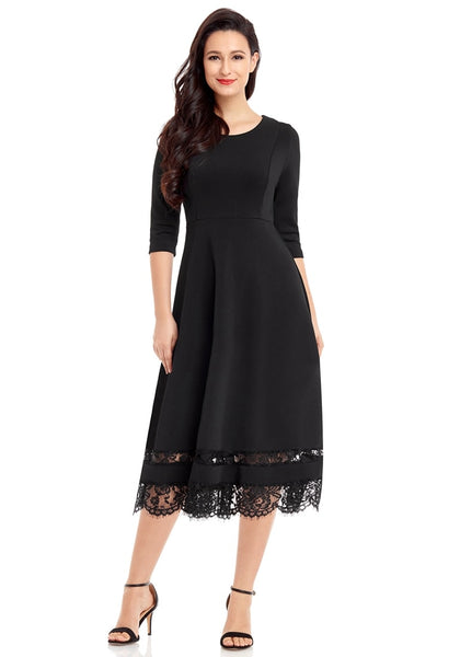 Front view of model in black scallop hem lace panel skater dress