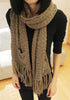Front view of model in brown tassel knit shawl wearing it like a scarf