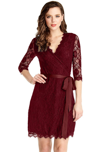 Front view of model in burgundy lace overlay plunge wrap-style dress with one hand on hip