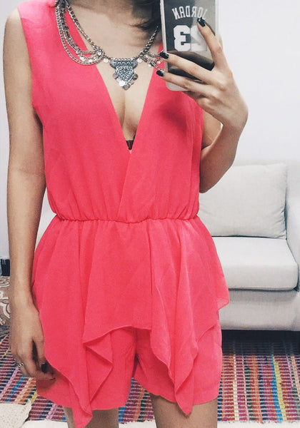 Front view of model in coral surplice peplum romper