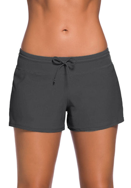 Front view of model in grey drawstring side-slit board shorts