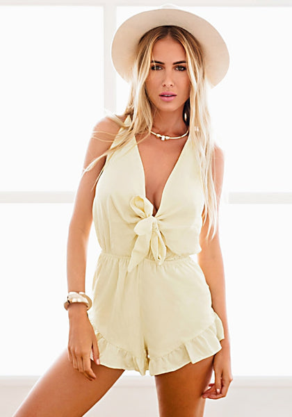 Front view of model in light yellow plunge bow-front romper