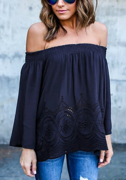 Front view of model in navy blue off-shoulder hollow out hem top