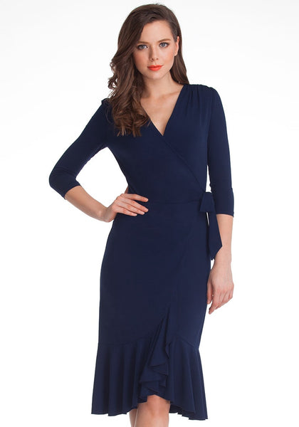 Full front shot of model in navy blue asymmetrical ruffled wrap dress