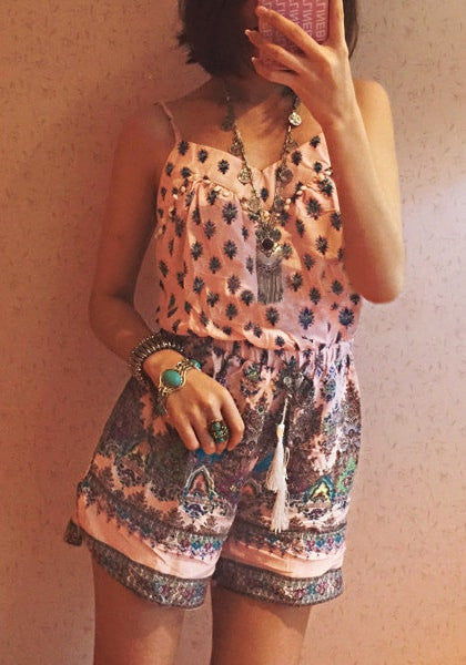 Front view of model in pink bohemian printed romper