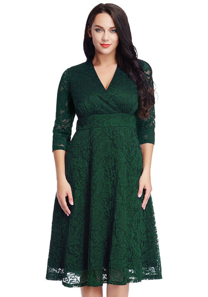 Front view of model in plus size green lace surplice midi dress