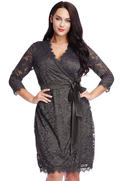 Front view of model in plus size grey lace crop sleeves wrap dress with hands at waist