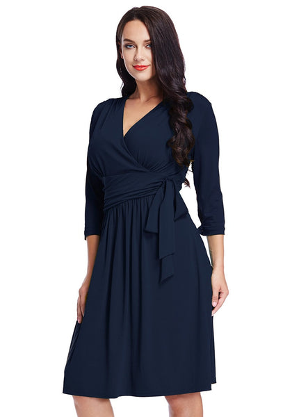 Front view of model in plus size navy blue plunge tie-side wrap dress