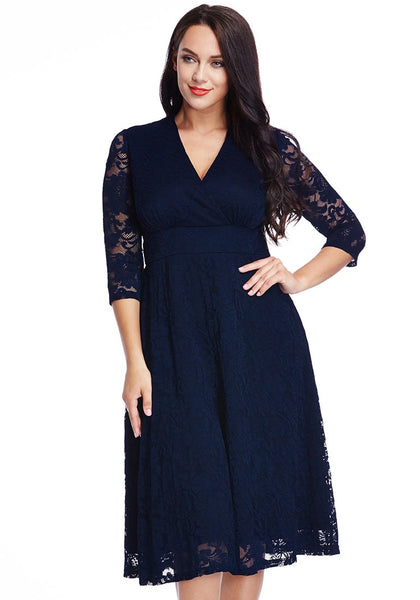 Front view of model in plus size navy lace surplice midi dress with one hand on legs