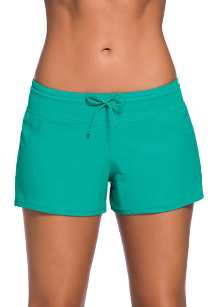 Front view of model in turquoise drawstring side-slit board shorts