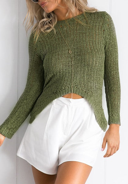 Front view of model in verdigris green high-low knit sweater slightly twisting her body