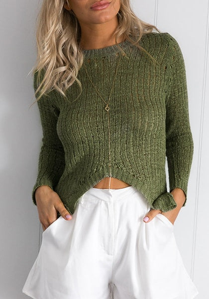 Front view of model in verdigris green high-low knit sweater with two hands in the pocket