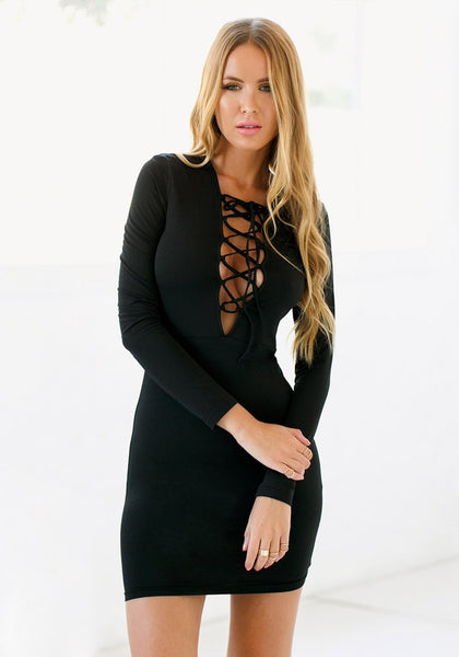Front view of model wearing a black lace-up mini dress