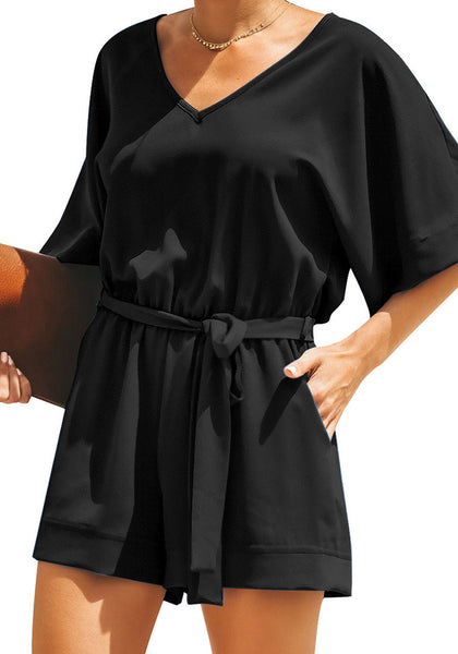 Front view of model wearing black V-neckline keyhole-back loose belted romper