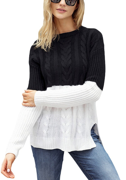 Front view of model wearing black and white color block side-slit cable knit sweater