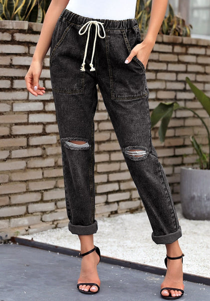 Front view of model wearing black drawstring-waist cuffed ripped boyfriend jeans