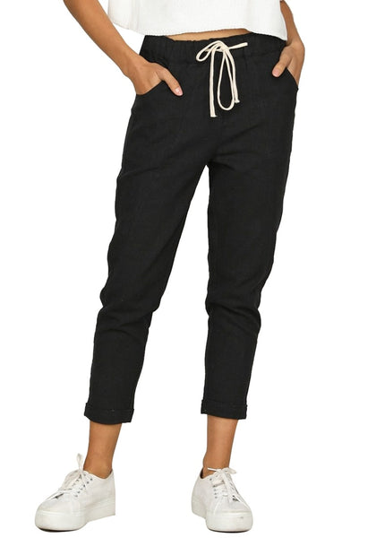 Front view of model wearing black drawstring-waist rolled-up cropped pants